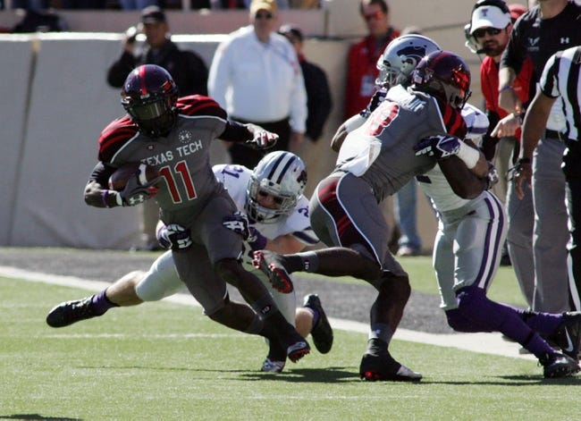Nov 9, 2013; Lubbock, TX, USA; Kansas State Wildcats defensive line backer Jonathan Truman (21) tackles Texas Tech Red Raiders wide receiver Jakeem Grant (11) in the first half at Jones AT&T Stadium. Mandatory Credit: Michael C. Johnson-USA TODAY Sports