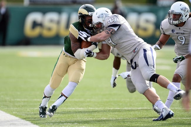 Nov 9, 2013; Fort Collins, CO, USA; Nevada Wolf Pack linebacker Jordan Dobrich (49) hits Colorado State Rams running back Donnell Alexander (7) in the first quarter at Hughes Stadium. Mandatory Credit: Ron Chenoy-USA TODAY Sports