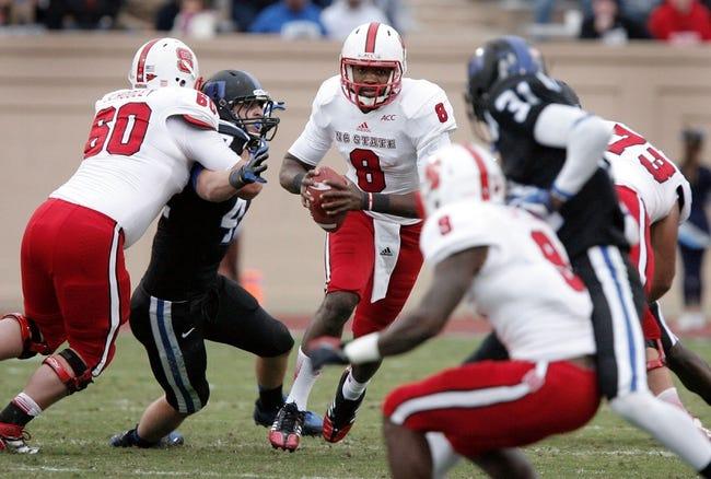 Nov 9, 2013; Durham, NC, USA; North Carolina State Wolfpack quarterback Brandon Mitchell (8) looks to run against the Duke Blue Devils defense at Wallace Wade Stadium. Mandatory Credit: Mark Dolejs-USA TODAY Sports