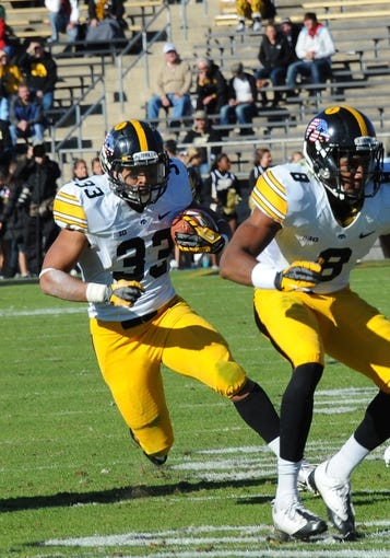Nov 9, 2013; West Lafayette, IN, USA; Iowa Hawkeyes running back Jordan Canzeri (33) runs behind the block of Iowa Hawkeyes wide receiver Don Shumpert (8) in the second half  at Ross Ade Stadium. Mandatory Credit: Sandra Dukes-USA TODAY Sports