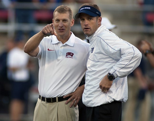 Nov 9, 2013; Las Vegas, NV, USA; UNLV Rebels head coach Bobby Hauck (left) points towards the camera while talking with Utah State Aggies head coach Matt Wells before an NCAA football game at Sam Boyd Stadium. Mandatory Credit: Stephen R. Sylvanie-USA TODAY Sports