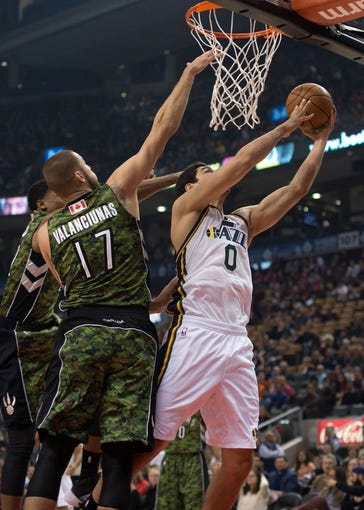 Nov 9, 2013; Toronto, Ontario, CAN; Utah Jazz center Enes Kanter (0) drives to the basket as Toronto Raptors center Jonas Valanciunas (17) goes for the block during the first period in a game at Air Canada Centre. 