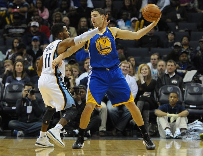 Nov 9, 2013; Memphis, TN, USA; Golden State Warriors shooting guard Klay Thompson (11) handles the ball against Memphis Grizzlies point guard Mike Conley (11) during the first quarter at FedExForum. Mandatory Credit: Justin Ford-USA TODAY Sports