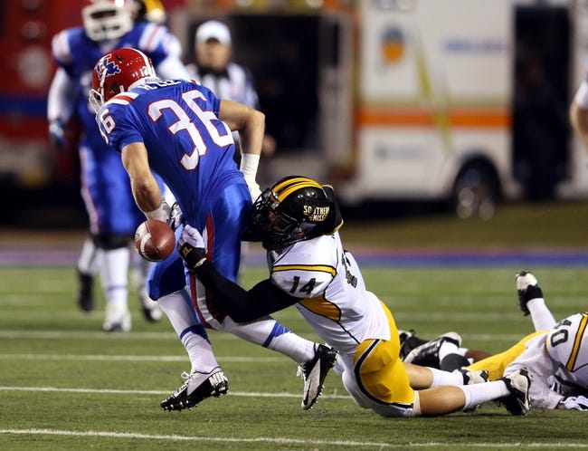 Nov 9, 2013; Ruston, LA, USA; Louisiana Tech Bulldogs running back Hunter Lee (36) fumbles after being hit by Southern Miss Golden Eagles linebacker Terrick Wright (14) during the second quarter at Joe Aillet Stadium. Mandatory Credit: Chuck Cook-USA TODAY Sports