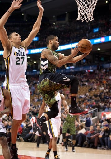 Nov 9, 2013; Toronto, Ontario, CAN; Toronto Raptors point guard D.J. Augustin (14) drives to the basket as Utah Jazz center Rudy Gobert (27) tries to defend during the fourth period in a game at Air Canada Centre. The Toronto Raptors won 115-91. Mandatory Credit: Nick Turchiaro-USA TODAY Sports
