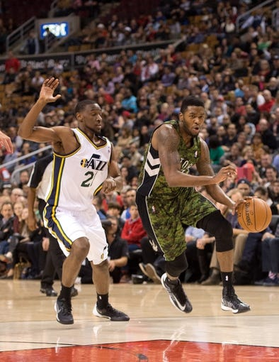 Nov 9, 2013; Toronto, Ontario, CAN; Toronto Raptors shooting guard Julyan Stone (77) drives to the basket as Utah Jazz shooting guard Ian Clark (21) tries to defend during the fourth period in a game at Air Canada Centre. The Toronto Raptors won 115-91. Mandatory Credit: Nick Turchiaro-USA TODAY Sports