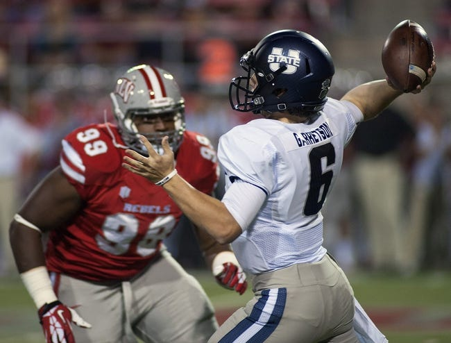 Nov 9, 2013; Las Vegas, NV, USA; Utah State Aggies quarterback Darell Garretson (6) looks to throw the ball as UNLV Rebels defensive lineman Tyler Gaston (99) approaches during an NCAA football game at Sam Boyd Stadium. Mandatory Credit: Stephen R. Sylvanie-USA TODAY Sports