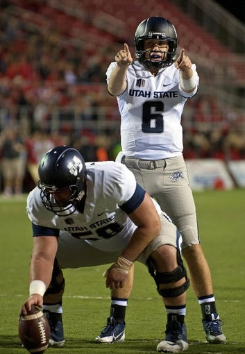 Nov 9, 2013; Las Vegas, NV, USA; Utah State Aggies quarterback Darell Garretson (6) calls a play at the line behind center Tyler Larsen (58) during a possession against the UNLV Rebels at an NCAA football game at Sam Boyd Stadium. Mandatory Credit: Stephen R. Sylvanie-USA TODAY Sports