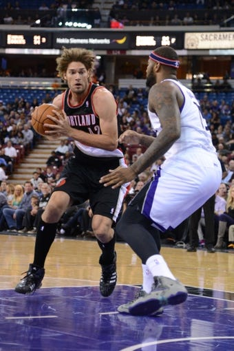 November 9, 2013; Sacramento, CA, USA; Portland Trail Blazers center Robin Lopez (42, left) dribbles the ball against Sacramento Kings center DeMarcus Cousins (15, right) during the first quarter at Sleep Train Arena. Mandatory Credit: Kyle Terada-USA TODAY Sports