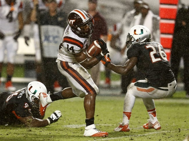 Nov 9, 2013; Miami Gardens, FL, USA;  Virginia Tech Hokies running back Trey Edmunds (14) runs between Miami Hurricanes defensive lineman Curtis Porter (96) and defensive back Rayshawn Jenkins (26) in the second half at Sun Life Stadium. Mandatory Credit: Robert Mayer-USA TODAY Sports