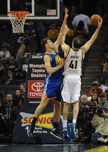 Nov 9, 2013; Memphis, TN, USA; Memphis Grizzlies center Kosta Koufos (41) takes a shot against Golden State Warriors center Ognjen Kuzmic (1) during the fourth quarter at FedExForum. The Grizzlies won 108-90.  Mandatory Credit: Justin Ford-USA TODAY Sports