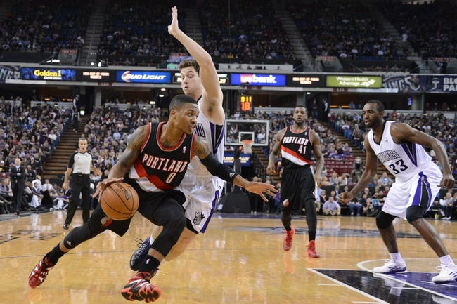 November 9, 2013; Sacramento, CA, USA; Portland Trail Blazers point guard Damian Lillard (0) dribbles the basketball against Sacramento Kings point guard Jimmer Fredette (7, second from left) during the second quarter at Sleep Train Arena. Mandatory Credit: Kyle Terada-USA TODAY Sports