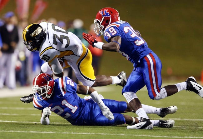Nov 9, 2013; Ruston, LA, USA; Southern Miss Golden Eagles running back Jalen Richard (30) is tackled by Louisiana Tech Bulldogs defensive backs Adairius Barnes (21) and Xavier Woods (39) during the second quarter at Joe Aillet Stadium. Mandatory Credit: Chuck Cook-USA TODAY Sports