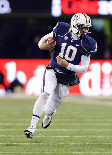 Nov 9, 2013; Seattle, WA, USA; Washington Huskies quarterback Cyler Miles (10) carries the ball against the Colorado Buffaloes during the 2nd half at Husky Stadium. Washington defeated Colorado 59-7. Mandatory Credit: Steven Bisig-USA TODAY Sports