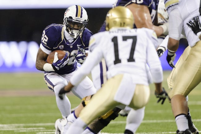Nov 9, 2013; Seattle, WA, USA; Washington Huskies running back Deontae Cooper (32) carries the ball while being defended by Colorado Buffaloes defensive back Marques Mosley (17) during the 2nd half at Husky Stadium. Washington defeated Colorado 59-7. Mandatory Credit: Steven Bisig-USA TODAY Sports