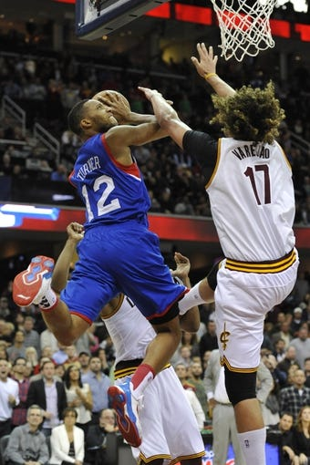 Nov 9, 2013; Cleveland, OH, USA; Philadelphia 76ers small forward Evan Turner (12) drives to the basket against Cleveland Cavaliers center Anderson Varejao (17) in the first overtime at Quicken Loans Arena. Mandatory Credit: David Richard-USA TODAY Sports