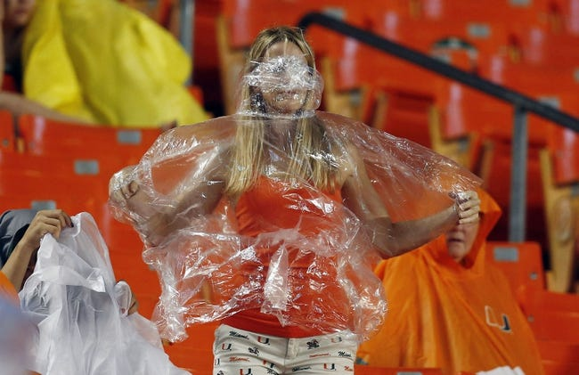 Nov 9, 2013; Miami Gardens, FL, USA; A fan covers up during a rain storm in the first quarter of a game between the Virginia Tech Hokies and Miami Hurricanes at Sun Life Stadium. Mandatory Credit: Robert Mayer-USA TODAY Sports