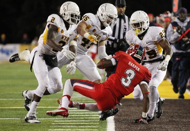 Nov 9, 2013; Laramie, WY, USA; Fresno State Bulldogs wide receiver Josh Harper (3) is tackled by Wyoming Cowboys Marqueston Huff (2) and Lucas Wacha (45) and Tim Hayes (29 during the first quarter at War Memorial Stadium. Mandatory Credit: Troy Babbitt-USA TODAY Sports