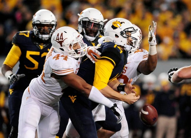 Nov 9, 2013; Morgantown, WV, USA; Texas Longhorns defensive end Jackson Jeffcoat (44) records a sack and forced fumble on West Virginia Mountaineers quarterback Paul Millard (14) at Milan Puskar Stadium. Mandatory Credit: Evan Habeeb-USA TODAY Sports