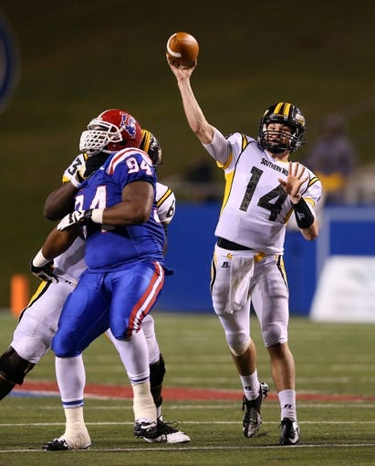 Nov 9, 2013; Ruston, LA, USA; Southern Miss Golden Eagles quarterback Nick Mullens (14) makes a throw while offensive linesman Fredrick Moore (63) blocks Louisiana Tech Bulldogs defensive tackle Shakeil Lucas (94) during the second half at Joe Aillet Stadium. Mandatory Credit: Chuck Cook-USA TODAY Sports