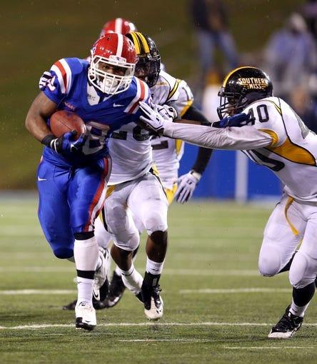 Nov 9, 2013; Ruston, LA, USA; Louisiana Tech Bulldogs running back Kenneth Dixon (28) runs away from Southern Miss Golden Eagles linebacker C.J. Perry (40) during the second half at Joe Aillet Stadium. Mandatory Credit: Chuck Cook-USA TODAY Sports