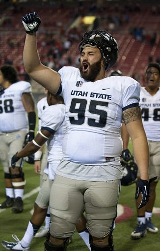 Nov 9, 2013; Las Vegas, NV, USA; Utah State Aggies defensive end Ricky Ali'ifua celebrates after the Aggies defeated the UNLV Rebels 28-24 at Sam Boyd Stadium. Mandatory Credit: Stephen R. Sylvanie-USA TODAY Sports