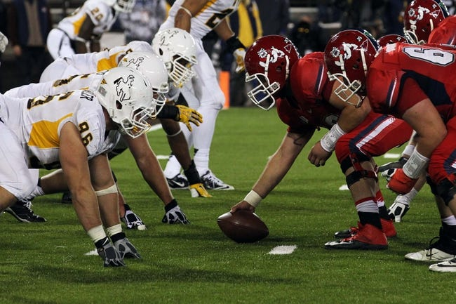 Nov 9, 2013; Laramie, WY, USA; Fresno State Bulldogs center Lars Bramer (56) at the line of scrimmage against the Wyoming Cowboys during the third quarter at War Memorial Stadium. Mandatory Credit: Troy Babbitt-USA TODAY Sports