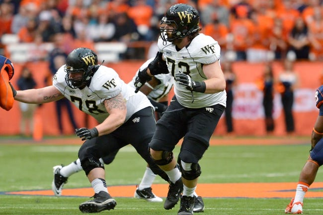 Nov 2, 2013; Syracuse, NY, USA; Wake Forest Demon Deacons offensive tackle Steven Chase (73) and guard Tyler Hayworth (78) block on a running play during the first quarter of a game against the Syracuse Orange at the Carrier Dome. Mandatory Credit: Mark Konezny-USA TODAY Sports