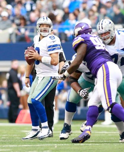 Nov 3, 2013; Arlington, TX, USA; Dallas Cowboys quarterback Tony Romo (9) looks to throw a pass against the Minnesota Vikings  at AT&T Stadium. Dallas beat Minnesota 27-23. Mandatory Credit: Tim Heitman-USA TODAY Sports