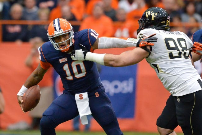 Nov 2, 2013; Syracuse, NY, USA; Syracuse Orange quarterback Terrel Hunt (10) avoids a tackle by Wake Forest Demon Deacons defensive end Zach Thompson (98) during the first quarter of a game at the Carrier Dome. Mandatory Credit: Mark Konezny-USA TODAY Sports