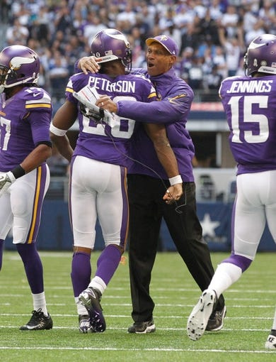 Nov 3, 2013; Arlington, TX, USA; Minnesota Vikings head coach Leslie Frazier hugs running back Adrian Peterson (28) after his touchdown in the game against the Dallas Cowboys at AT&T Stadium. Dallas beat Minnesota 27-23. Mandatory Credit: Tim Heitman-USA TODAY Sports