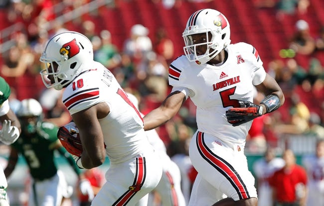 Oct 26, 2013; Tampa, FL, USA; Louisville Cardinals quarterback Teddy Bridgewater (5) hands the ball off to running back Dominique Brown (10) against the South Florida Bulls during the first quarter  at Raymond James Stadium. Mandatory Credit: Kim Klement-USA TODAY Sports