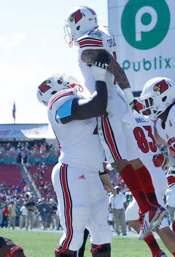 Oct 26, 2013; Tampa, FL, USA; Louisville Cardinals wide receiver Damian Copeland (7) is picked up by offensive linesman John Miller (70) after he scored a touchdown against the South Florida Bulls during the first quarter  at Raymond James Stadium. Mandatory Credit: Kim Klement-USA TODAY Sports