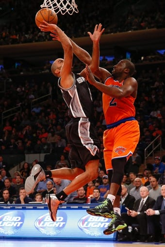Nov 10, 2013; New York, NY, USA;  San Antonio Spurs point guard Tony Parker (9) shoots over New York Knicks point guard Raymond Felton (2) during the third quarter at Madison Square Garden. Spurs won 120-89.  Mandatory Credit: Anthony Gruppuso-USA TODAY Sports