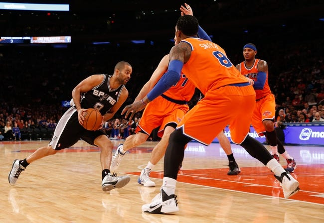 Nov 10, 2013; New York, NY, USA;  San Antonio Spurs point guard Tony Parker (9) drives between New York Knicks shooting guard J.R. Smith (8) and power forward Andrea Bargnani (77) during the third quarter at Madison Square Garden. Spurs won 120-89.  Mandatory Credit: Anthony Gruppuso-USA TODAY Sports