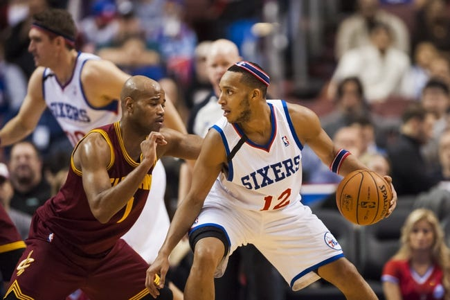 Nov 8, 2013; Philadelphia, PA, USA; Philadelphia 76ers guard Evan Turner (12) is defended by Cleveland Cavaliers guard Jarrett Jack (1) during the fourth quarter at Wells Fargo Center. The Sixers defeated the Cavaliers 94-79. Mandatory Credit: Howard Smith-USA TODAY Sports