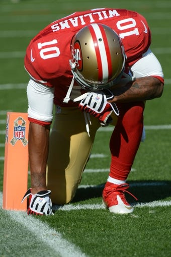 November 10, 2013; San Francisco, CA, USA; San Francisco 49ers wide receiver Kyle Williams (10) kneels in the end zone next to a pylon with the military tribute logo before the game against the Carolina Panthers at Candlestick Park. Mandatory Credit: Kyle Terada-USA TODAY Sports