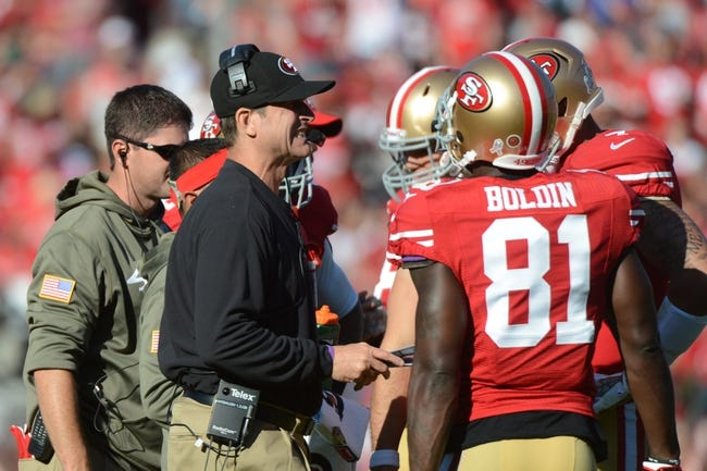 November 10, 2013; San Francisco, CA, USA; San Francisco 49ers head coach Jim Harbaugh (left) reacts in a huddle against the Carolina Panthers during the second quarter at Candlestick Park. The Panthers defeated the 49ers 10-9. Mandatory Credit: Kyle Terada-USA TODAY Sports
