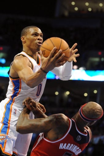 Nov 10, 2013; Oklahoma City, OK, USA; Oklahoma City Thunder point guard Russell Westbrook (0) attempts a shot against Washington Wizards power forward Al Harrington (7) during the third quarter at Chesapeake Energy Arena. Mandatory Credit: Mark D. Smith-USA TODAY Sports
