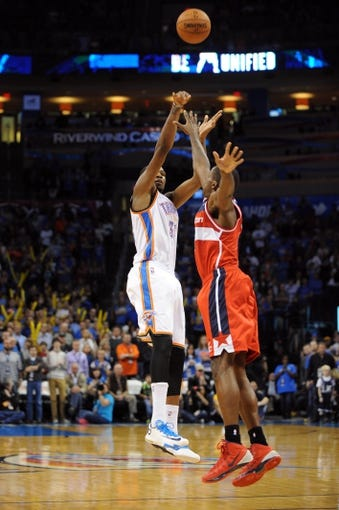 Nov 10, 2013; Oklahoma City, OK, USA; Oklahoma City Thunder small forward Kevin Durant (35) shoots a 3 point shot against Washington Wizards shooting guard Bradley Beal (3) in overtime at Chesapeake Energy Arena. Mandatory Credit: Mark D. Smith-USA TODAY Sports