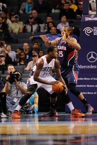 Nov 11, 2013; Charlotte, NC, USA; Charlotte Bobcats forward Michael Kidd Gilchrist (14) is defended by Atlanta Hawks forward center Al Horford (15) during the game at Time Warner Cable Arena. Mandatory Credit: Sam Sharpe-USA TODAY Sports