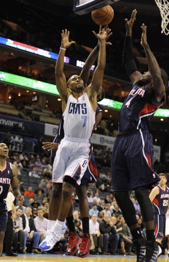 Nov 11, 2013; Charlotte, NC, USA; Charlotte Bobcats guard Ramon Sessions (7) shoots the ball as Atlanta Hawks forward Paul Millsap (4) defends in the fourth quarter at Time Warner Cable Arena. The Hawks won 103-94. Mandatory Credit: Sam Sharpe-USA TODAY Sports