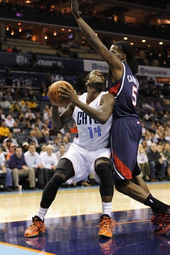Nov 11, 2013; Charlotte, NC, USA; Charlotte Bobcats forward Michael Kidd Gilchrist (14) shoots the ball as Atlanta Hawks forward DeMarre Carroll (5) defends in the fourth quarter at Time Warner Cable Arena. The Hawks won 103-94. Mandatory Credit: Sam Sharpe-USA TODAY Sports