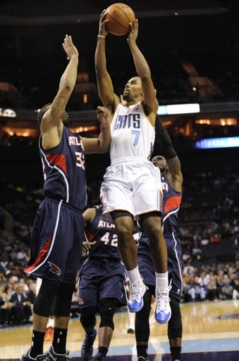 Nov 11, 2013; Charlotte, NC, USA; Charlotte Bobcats guard Ramon Sessions (7) shoots the ball as Atlanta Hawks forward Mike Scott (32) defends during the third quarter at Time Warner Cable Arena. The Hawks won 103-94. Mandatory Credit: Sam Sharpe-USA TODAY Sports