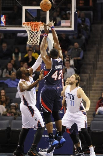 Nov 11, 2013; Charlotte, NC, USA; Atlanta Hawks forward center Elton Brand (42) shoots the ball as Charlotte Bobcats center Al Jefferson (25) and forward Josh McRoberts (11) defend in the fourth quarter at Time Warner Cable Arena. The Hawks won 103-94. Mandatory Credit: Sam Sharpe-USA TODAY Sports