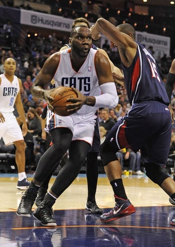 Nov 11, 2013; Charlotte, NC, USA; Charlotte Bobcats center Al Jefferson (25) dribbles the ball past Atlanta Hawks forward center Al Horford during the third quarter at Time Warner Cable Arena. The Hawks won 103-94. Mandatory Credit: Sam Sharpe-USA TODAY Sports