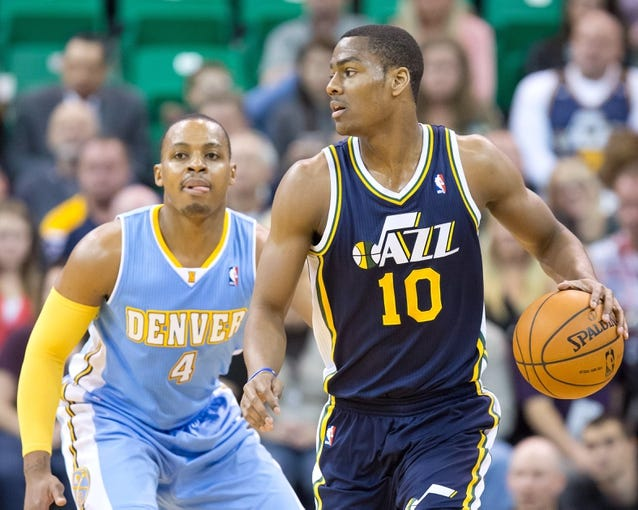 Nov 11, 2013; Salt Lake City, UT, USA; Utah Jazz point guard Alec Burks (10) controls the ball while defended by Denver Nuggets shooting guard Randy Foye (4) during the first half at EnergySolutions Arena. Mandatory Credit: Russ Isabella-USA TODAY Sports
