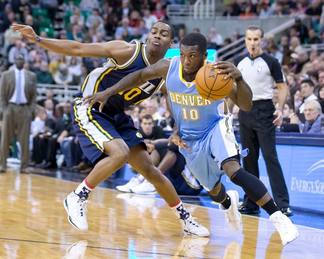 Nov 11, 2013; Salt Lake City, UT, USA; Denver Nuggets point guard Nate Robinson (10) dribbles around Utah Jazz point guard Alec Burks (10) during the first half at EnergySolutions Arena. Mandatory Credit: Russ Isabella-USA TODAY Sports
