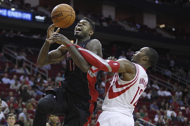 Nov 11, 2013; Houston, TX, USA; Toronto Raptors power forward Amir Johnson (15) is fouled by Houston Rockets center Dwight Howard (12) during the fourth quarter at Toyota Center. The Rockets won 110-104.  Mandatory Credit: Andrew Richardson-USA TODAY Sports