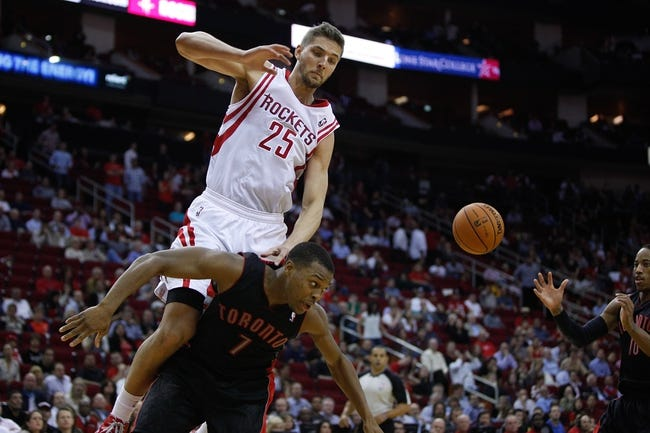 Nov 11, 2013; Houston, TX, USA; Toronto Raptors point guard Kyle Lowry (7) is fouled by Houston Rockets small forward Chandler Parsons (25) during the first overtime period at Toyota Center. Mandatory Credit: Andrew Richardson-USA TODAY Sports